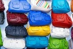 许多用皮革包盖提包不同的颜色和大小与口袋和金属钩子 上色提包染黑,蓝色,红色,黄色,绿色, w 图库摄影