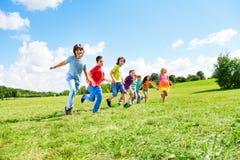 许多男孩和女孩跑 免版税库存照片