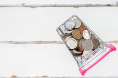 许多的顶视图在微型购物的纸盒白色木地板的硬币与拷贝空间的空白 库存图片