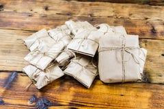 许多礼物包裹了在木背景的牛皮纸 一个大礼物 库存图片