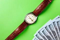 许多票据100美元,我们钞票,与金钱现金货币特写镜头的绿色背景,相当金钱,时钟价值的概念时间 免版税库存图片