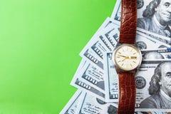 许多票据100美元,我们钞票,与金钱现金货币特写镜头的绿色背景,相当金钱,时钟价值的概念时间 图库摄影
