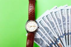 许多票据100美元,我们钞票,与金钱现金货币特写镜头的绿色背景,相当金钱,时钟价值的概念时间 免版税库存照片