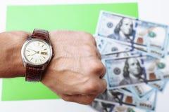 许多票据100美元,我们钞票,与金钱现金货币特写镜头的绿色背景,相当金钱,时钟价值的概念时间 库存图片