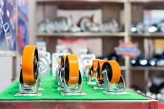 许多种类和大小五颜六色工业存贮的铸工轮子在架子 免版税库存图片