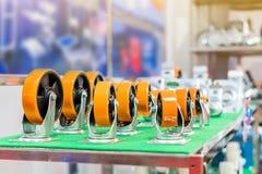 许多种类和大小五颜六色工业存贮的铸工轮子在架子 库存照片