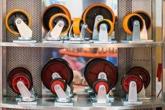 许多种类和大小五颜六色工业存贮的铸工轮子在架子 免版税库存照片