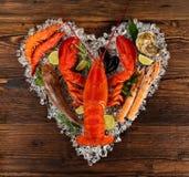 许多种类在心脏形状的海鲜 服务在被击碎的冰 免版税库存照片