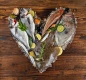 许多种类在心脏形状的海鲜 服务在被击碎的冰 免版税库存图片
