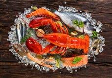 许多种类海鲜,服务在被击碎的冰,安置在老木板条 免版税库存照片