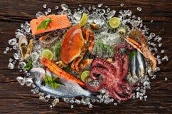 许多种类海鲜,服务在被击碎的冰,安置在老木板条 库存照片