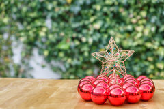 许多红色圣诞节球围拢的圣诞节星,在木头 图库摄影