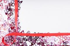 许多红色在白色背景、框架和空间的心脏形状红色丝带弓文本的 免版税图库摄影