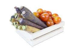 许多红萝卜和蕃茄与裁减路线在木板箱箱子是 库存照片