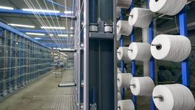 许多线团在工厂机架转动,缠绕与螺纹 工业纺织品生产线 股票视频