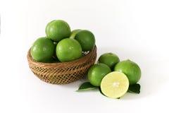 许多绿色柠檬在一个木篮子 并且某些与柠檬切片的外部在边切成了两半 免版税图库摄影