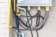 许多缆绳接通在砖墙上的一个插口 使用的危险 免版税图库摄影