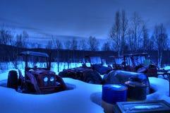 许多老充满活力的被风化的拖拉机在多雪的零件围场 免版税库存图片