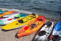 许多色的皮船在海滩,概念连续站立 免版税库存图片