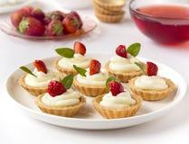 许多蛋糕或微型馅饼用新鲜水果、打好的奶油和薄菏 免版税图库摄影