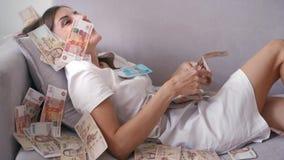 许多钞票在慢动作的空气天花板飞行 女孩说谎和在她的很多金钱秋天 愉快的妇女高兴 股票视频