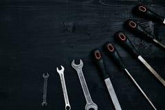 许多锋利的钢刀片和板钳系列在黑木背景 免版税库存照片