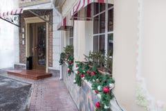 许多闪烁,发光的圣诞树球,在餐馆的窗口,咖啡馆的装饰 砖墙,与元素的门 库存照片