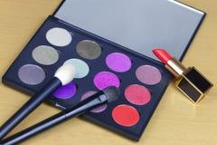 许多颜色大眼影调色板在淡紫色,紫罗兰色和红色口气的,与两把化妆刷子和被打开的红色口红在豪华 免版税库存图片