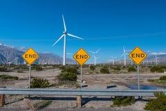 许多风力机在有3个末端标志的沙漠 图库摄影