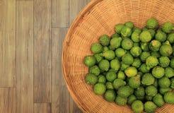 许多香柠檬在藤条篮子投入了在自然木地板 免版税库存照片