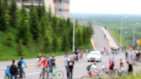 许多骑自行车者和步行者沿路前进 用绿草和毛皮树盖的小山 股票录像