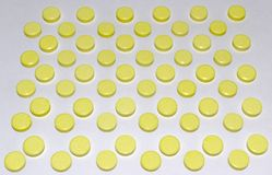 许多黄色药片,安排按交错排列顺序 免版税库存图片