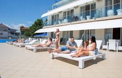 许多年轻人和妇女基于旅馆` s夏天区域 小组愉快,美丽和青年人松弛和 免版税库存图片