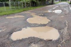 许多钻孔和在柏油路的洪水 免版税库存照片