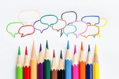 许多从颜色铅笔的五颜六色的讲话泡影在白皮书 免版税库存照片
