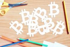许多bitcoin标志从在木书桌上的纸被删去 库存照片