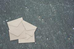 许多od信封为送在沙子纹理背景的邮件暗示 免版税库存图片