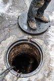 建设中都市的路,涂柏油过程中,工作者临近下水道出入孔,脚片段 库存照片