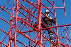 设定铁脚手架的未认出的工作者在建筑 免版税库存图片