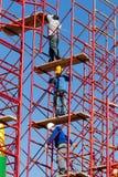 设定铁脚手架的未认出的工作者在建筑 图库摄影