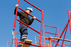 设定铁脚手架的未认出的工作者在建筑 库存图片