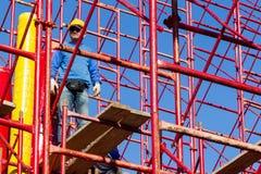 设定铁脚手架的未认出的工作者在建筑 免版税库存照片