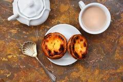 设想用早晨咖啡和蛋糕Pasteis de nata,从葡萄牙的典型的酥皮点心自然大理石表面上 库存图片