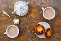 设想用早晨咖啡和蛋糕Pasteis de nata,从葡萄牙的典型的酥皮点心自然大理石表面上 免版税库存照片