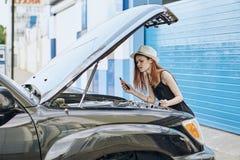 设法一个白色的帽子的年轻美丽的妇女修理一辆汽车在夏天在城市 库存图片