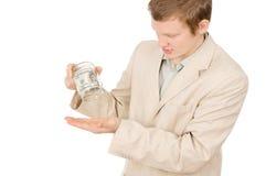 设法一个年轻的人从一个玻璃容器提取金钱 免版税库存图片