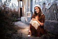 设法一件土气的礼服的哀伤的妇女坐在老砖墙附近在老房子里和穿戴一双白色鞋子 灰姑娘样式 图库摄影