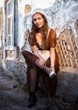 设法一件土气的礼服的哀伤的妇女坐在老砖墙附近在老房子里和穿戴一双白色鞋子 灰姑娘样式 库存图片