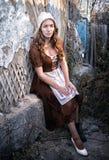 设法一件土气的礼服的哀伤的妇女坐在老砖墙附近在老房子里和穿戴一双白色鞋子 灰姑娘样式 免版税库存图片