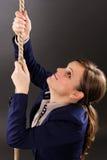 设法一名年轻的女实业家的特写镜头画象攀登绳索 库存图片